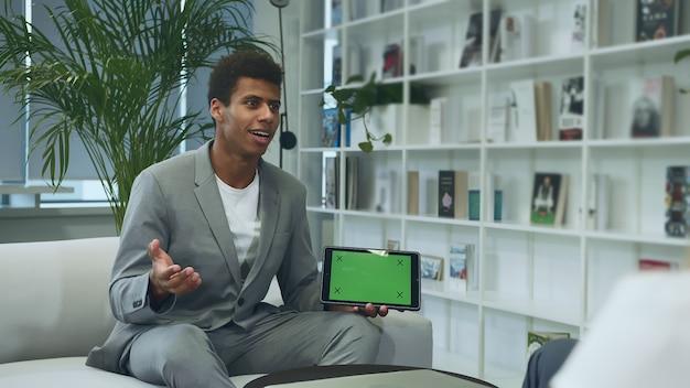 Hombre formal negro haciendo presentación con tableta con pantalla chromakey verde.