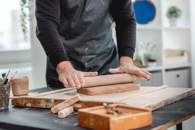 Hombre formando molde de arcilla de alfarería en el taller