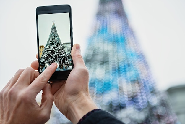 El hombre está fotografiando un árbol de navidad con el teléfono inteligente.
