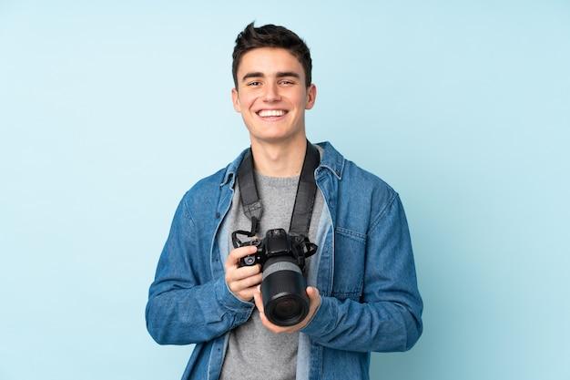 Hombre fotógrafo adolescente aislado en azul