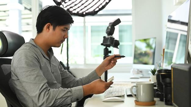 Un hombre fotógrafo independiente está trabajando en su proyecto en el escritorio de la oficina con varias computadoras.