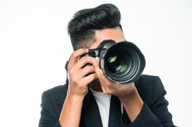 Hombre fotógrafo indio sosteniendo su cámara sobre un fondo blanco.