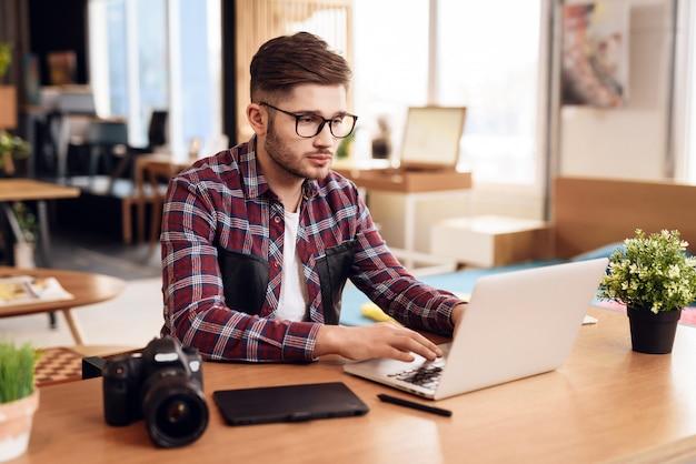 Hombre del freelancer que mecanografía en el ordenador portátil que se sienta en el escritorio.