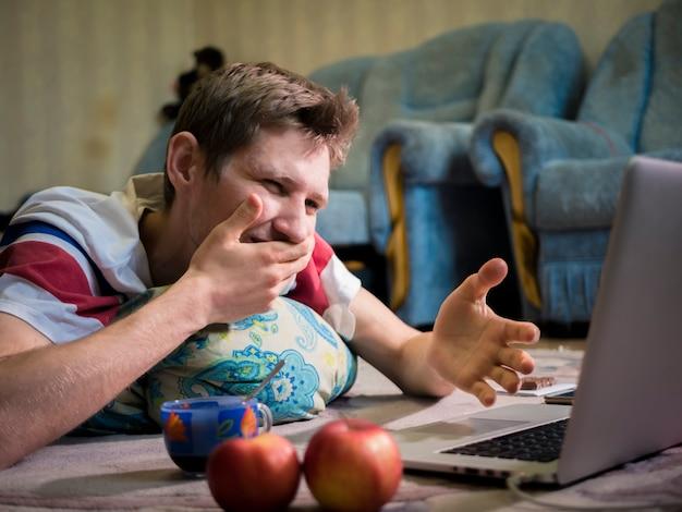 Hombre frente a laptop sorprendido sorprendido y conmocionado de emoción