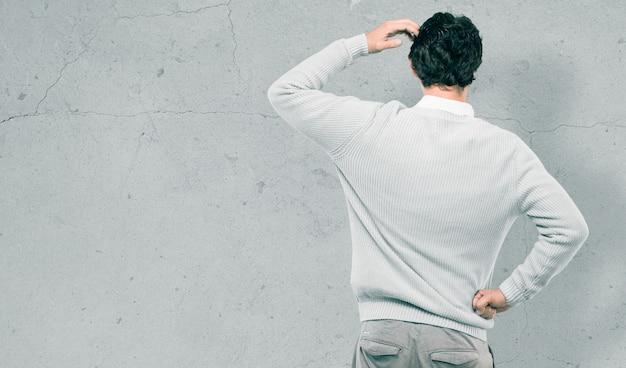 Hombre fresco joven contra la pared de cemento