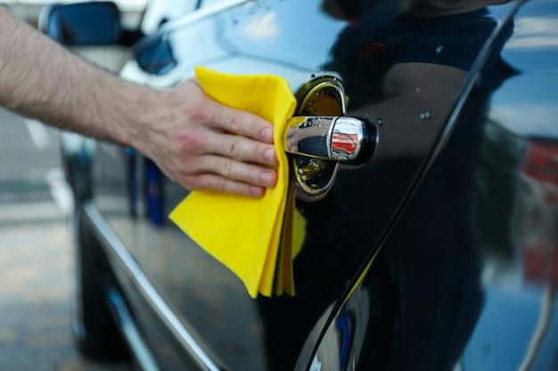 Un hombre frota un auto. lavado de autos. concepto de coche claro