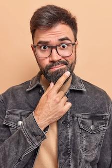 Hombre frunce los labios mantiene la mano en la barbilla se siente avergonzado tiene algunas dudas antes de tomar una decisión importante usa chaqueta negra y anteojos posa en interiores