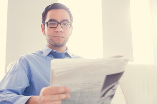 Hombre frunciendo el ceño mirando a cámara y sosteniendo un periódico
