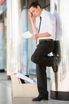 Hombre frustrado encendido en el traje que se coloca cerca de oficina.