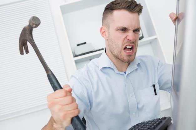 Hombre frustrado golpeando el monitor de la computadora con martillo