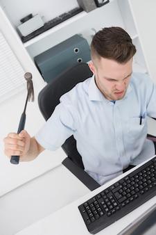 Hombre frustrado golpeando el teclado del monitor de la computadora con martillo