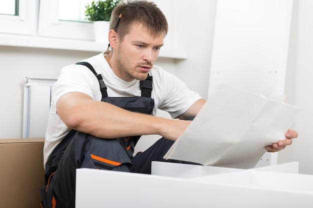 Hombre frustrado leyendo instrucciones y armando muebles de autoensamblaje. bricolaje, nuevo hogar y concepto de mudanza