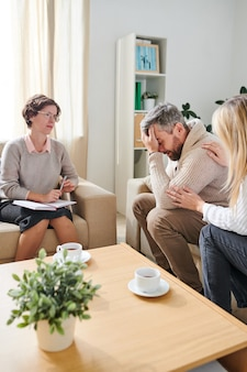 Hombre frustrado llorando mientras su esposa lo apoyaba en la terapia sessi