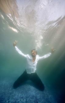 Hombre frustrado que se hunde en la piscina profunda