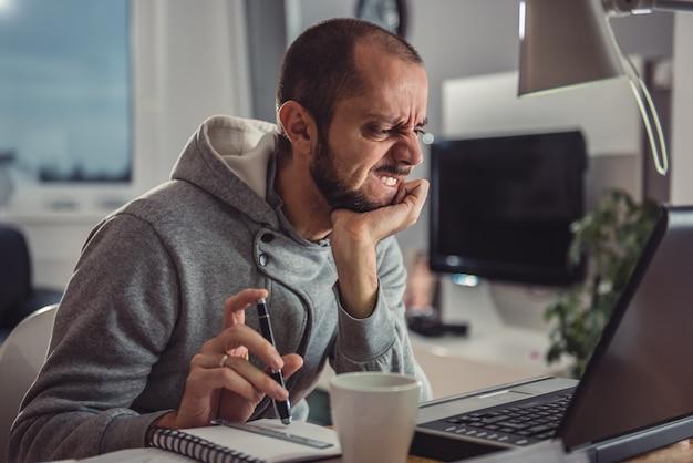 Hombre frustrado que trabaja en la computadora portátil