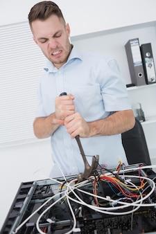 Hombre frustrado que usa el martillo para sacar los cables de la cpu
