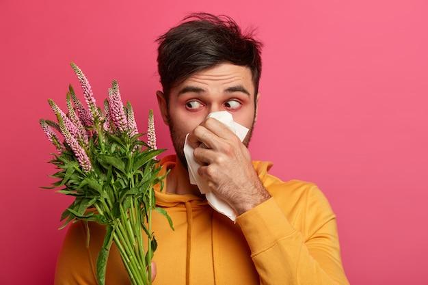 El hombre frustrado se suena la nariz con un pañuelo, tiene enrojecimiento alrededor de los ojos, síntomas de alergia, tiene un aspecto poco saludable, se concentra en la flor, sufre de rinitis, reacción alérgica. personas y enfermedad