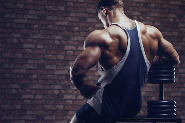 Hombre fuerte culturista bombeo de los músculos de la espalda