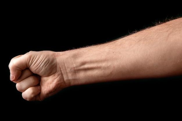 Un hombre fuerte levantó su puño sobre negro.