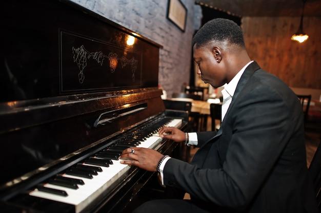 Hombre fuerte y poderoso en traje negro toca el piano