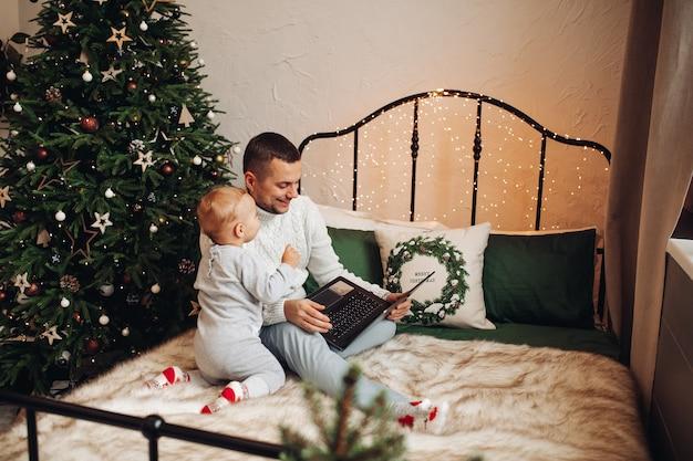 Un hombre fuerte con ropa de año nuevo viendo una serie de televisión en la cama con un niño