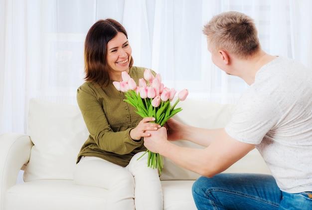 Hombre fuerte saludando a su esposa de vacaciones con ramo floral festivo