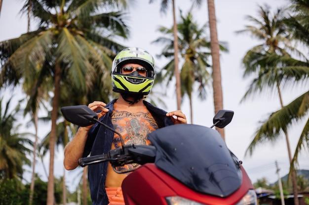 Hombre fuerte tatuado en el campo de la selva tropical con moto roja