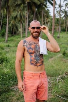Hombre fuerte tatuado en el campo tropical de la selva sin camisa