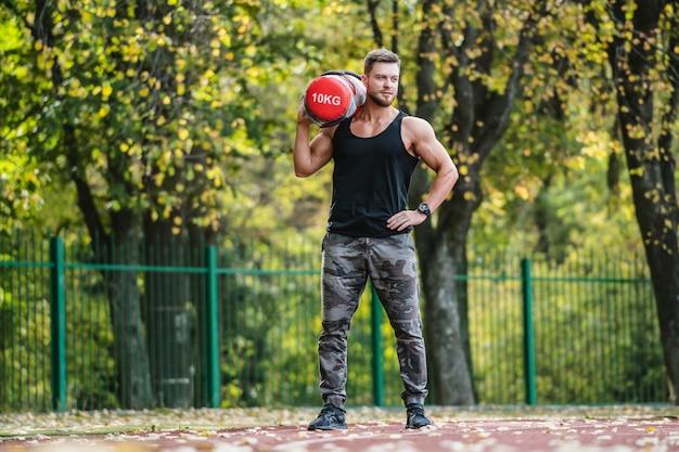 Hombre fuerte, trabajo físico al aire libre. levantar herramientas pesadas. guapo deportista. joven culturista. trabajando en un campo deportivo. hombre confiado