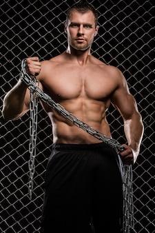 Hombre fuerte en la valla con cadenas