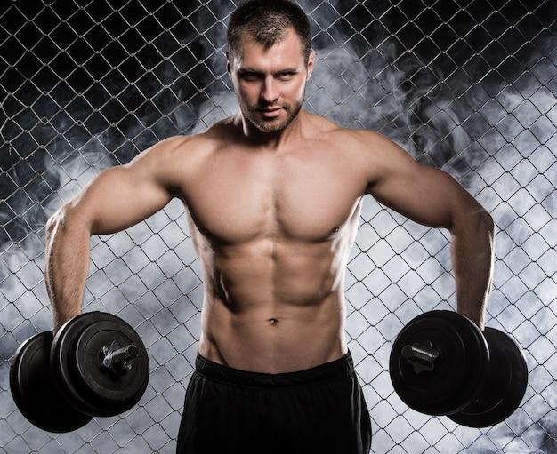 Hombre fuerte en la valla con pesas