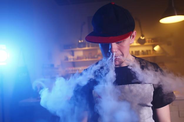 El hombre fuma un cigarrillo electrónico en la tienda de vape