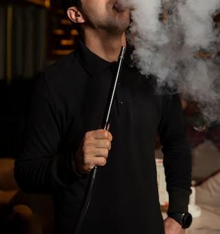 El hombre fuma shisha y retira el humo