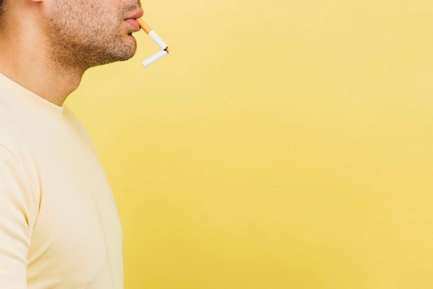 Hombre fumando un cigarrillo con espacio de copia
