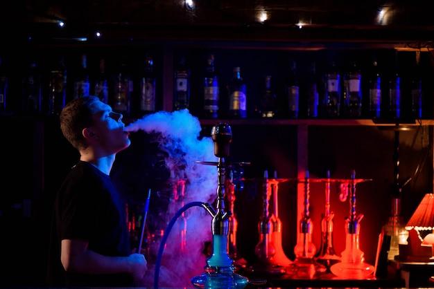 Hombre fumando pipa de narguile tradicional y exhalando humo en la cafetería hookah.