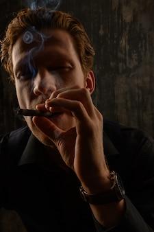 Hombre y fumar cigarrillo. retrato de estudio sobre fondo oscuro