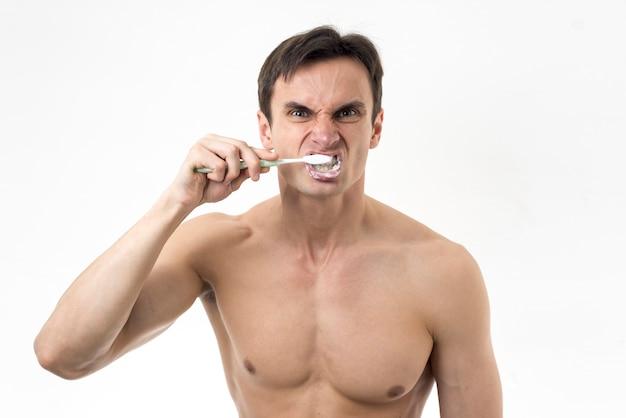 Hombre furiosamente cepillándose los dientes
