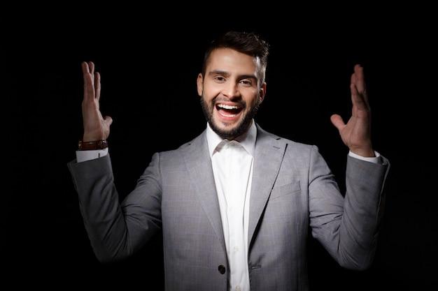 Hombre furioso gritando cierra las orejas con los dedos sobre la pared gris