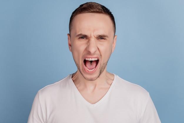Hombre furioso con mueca de mal humor en su cara boca abierta en grito conflicto loco loco aislado sobre fondo azul