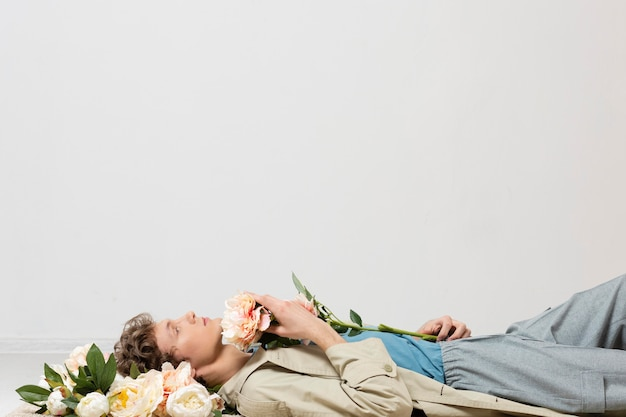 Hombre con gabardina sosteniendo flores