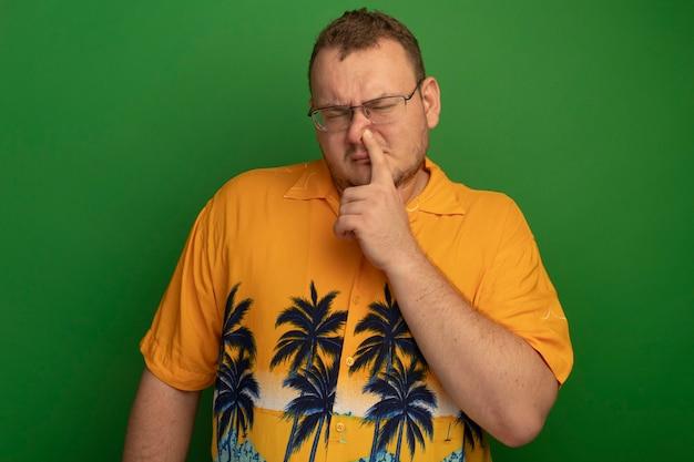 Hombre de gafas y camisa naranja cerrando la nariz con el dedo mirando confundido de pie sobre la pared verde