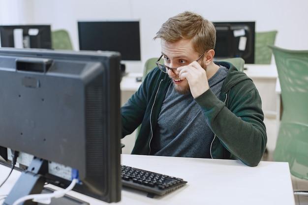 Hombre de las gafas. estudiante en clase de informática. la persona usa una computadora.