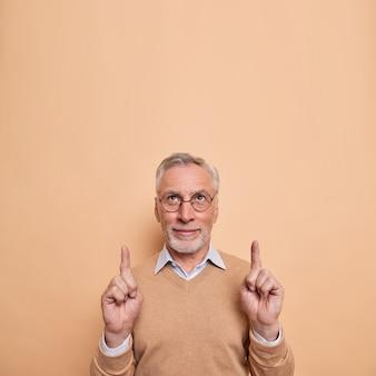 El hombre con gafas indica hacia arriba echa un vistazo a una promoción genial que muestra un anuncio en la parte superior vestido con ropa casual aislado en marrón
