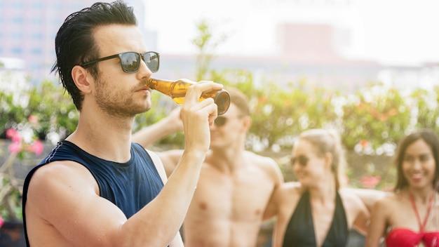 Hombre de gafas negras con bebida de botella de cerveza con niño y amigas en bikini suite de fiesta.