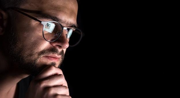 Un hombre con gafas en la oscuridad mira el espacio de copia de la pantalla de la computadora