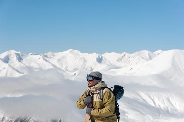 Hombre con gafas protectoras de esquí y un traje de abrigo, con una tabla de snowboard en sus manos, se eleva a la pista