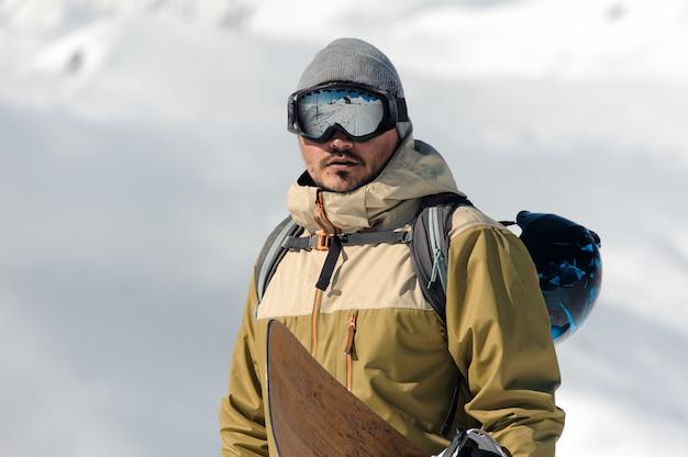 Hombre con gafas protectoras de esquí y un traje de abrigo, con una tabla de snowboard en sus manos, sube a la pista contra las montañas cubiertas de nieve.