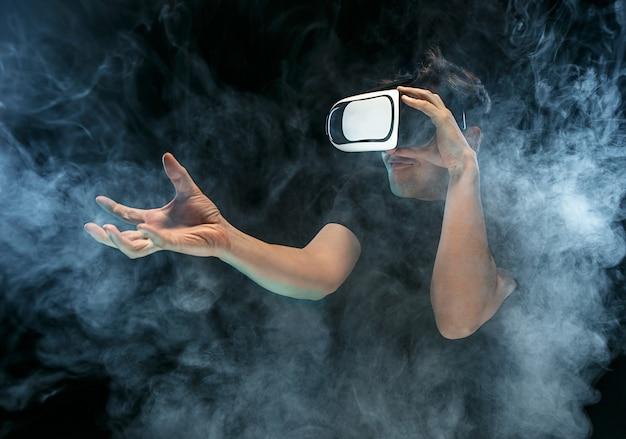 El hombre con gafas de realidad virtual. concepto de tecnología futura. estudio negro ahumado