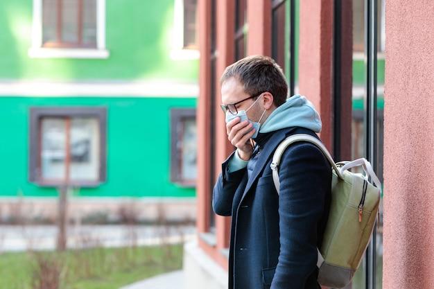 Hombre con gafas sintiéndose enfermo al aire libre, tosiendo, usando una máscara protectora contra enfermedades infecciosas transmisibles, alergia al polen, protección contra virus