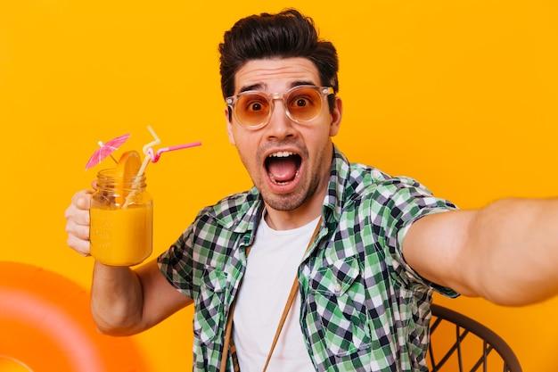 Hombre con gafas de sol y camisa verde toma un selfie y mira a la cámara con sorpresa. retrato de chico con copa de cóctel en espacio aislado.